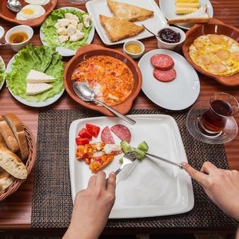 Van bovenaf een uitgebreid ontbijt met omelet en glas thee en menselijke hand in servetten