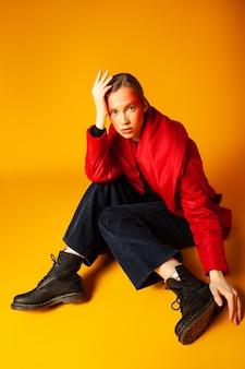 Van bovenaf eenzaam vrouwelijk model met creatieve make-up inwikkeling in rode oversized jas en wegkijken tegen gele achtergrond