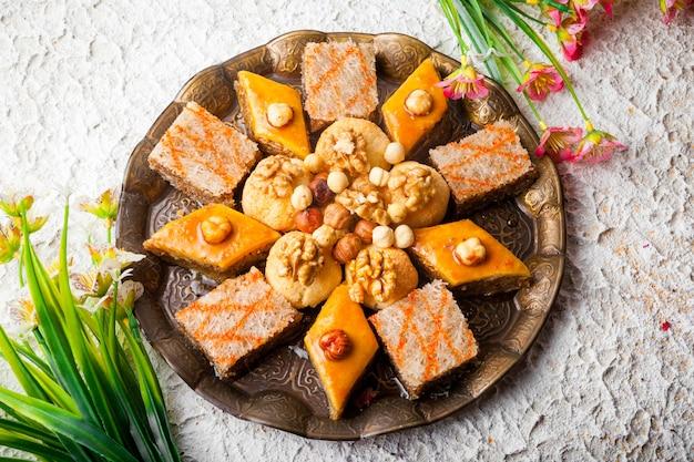 Van bovenaf geassorteerde gebakken met baklava en baklava sheki en bloemen in gerookte vis