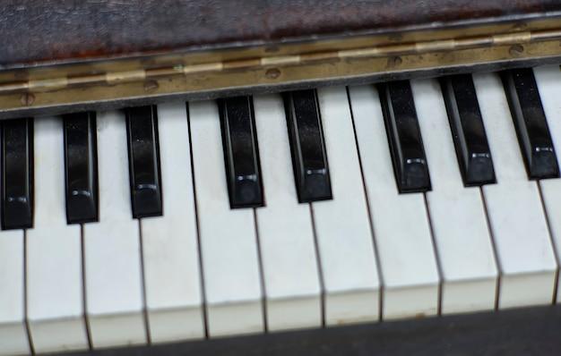 Van bovenaf genomen enkele ivoren toetsen van een antieke piano.