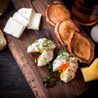 Van bovenaf gepocheerd ei met pannenkoeken en kopje thee en kaas in bord kookgerei