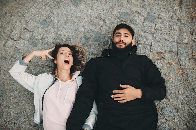 Van bovenaf geschoten o man en vrouw die vrolijk naar de camera gebaren terwijl ze op geplaveide stoep lagen