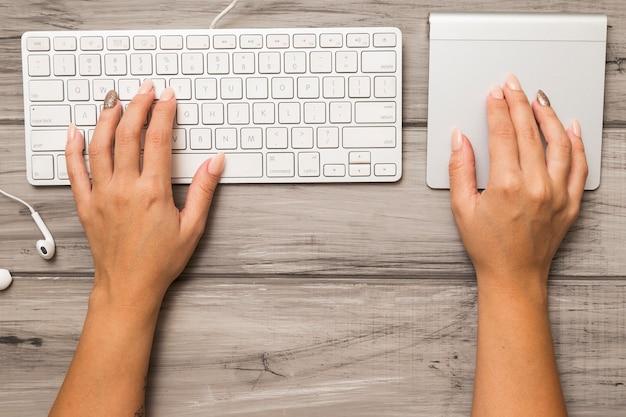 Van bovenaf handen met toetsenbord en trackpad