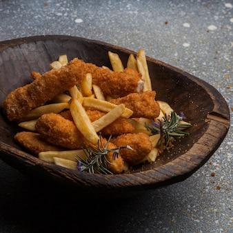 Van bovenaf kipnuggets met frietjes in houten plaat
