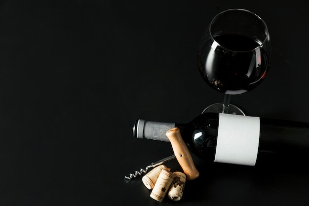 Van bovenaf kurkentrekker in de buurt van fles en wijnglas