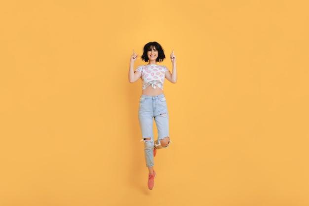 Van bovenaf lachen brunette vrouw in shirt en spijkerbroek met handen op gezichtsniveau op oranje achtergrond