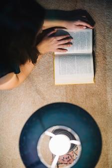 Van bovenaf lezen van de vrouw in de buurt van de lamp