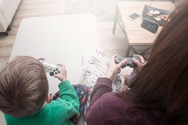 Van bovenaf moeder en zoon die videogames spelen