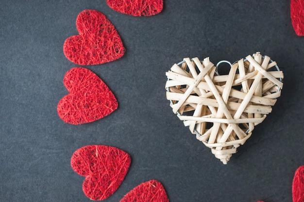 Van bovenaf samenstelling van decoratieve witte en rode symbolen van hart op zwart