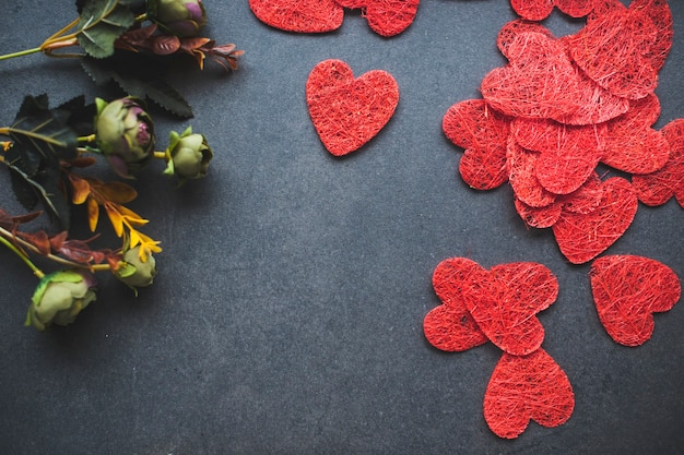 Van bovenaf samenstelling van ornament rode symbolen van hart in de buurt van rij verse bloemen op zwart