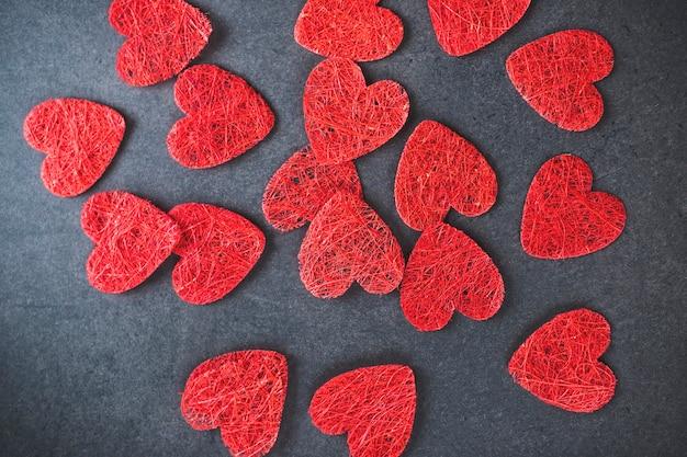 Van bovenaf samenstelling van ornament rode symbolen van hart verspreid over zwart