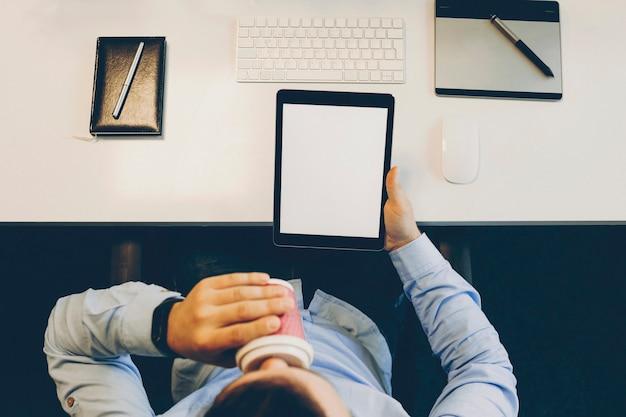 Van bovenaf schot van anonieme man verse warme drank drinken en tablet met leeg scherm te houden terwijl zittend aan tafel in moderne kantoor. knip man met tablet genieten van warme drank in kantoor