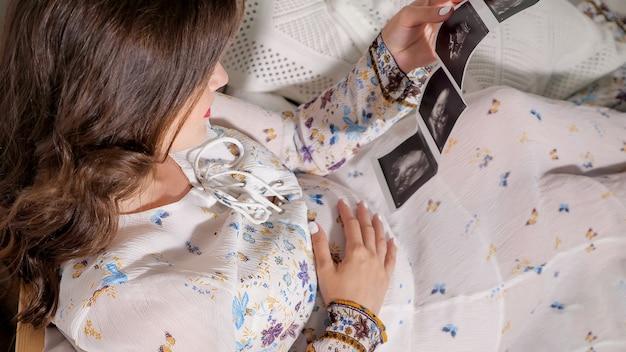 Van bovenaf schot van zwangere vrouw met foetale scan zittend op bed. concept van zwangere vrouwen gezond en gezondheidszorg.