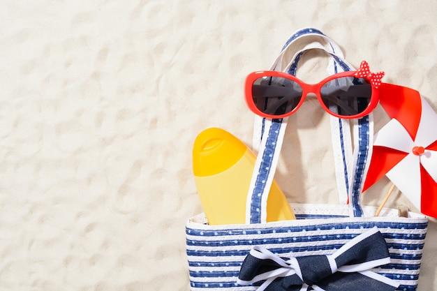 Van bovenaf shot van tas met lotion, zonnebril en kleurrijk vuurrad op zand
