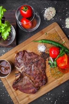 Van bovenaf steak met tomaat en papier in steak board