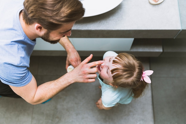 Van bovenaf vader smeren crème op neus van dochter