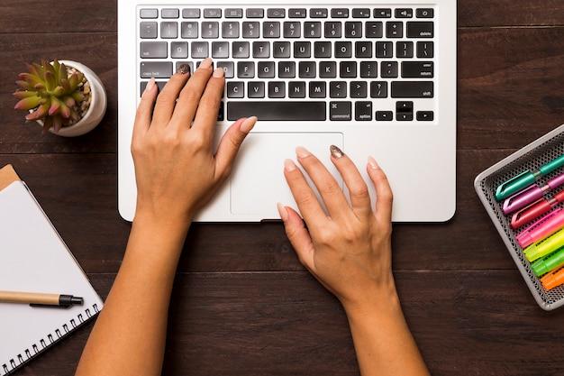 Van bovenaf van vrouwelijke handen die op laptop werken
