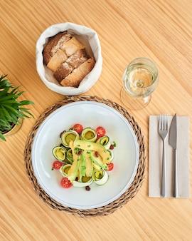 Van bovenaf verse rauwe courgettesalade met tomaten en avocado vergezeld van een glas witte wijn en een stoffen mand met brood