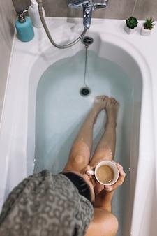 Van bovenaf vrouw koffie drinken in bad
