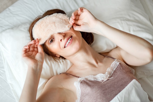 Van bovenaf wordt het beeld gefilmd van een gezonde jonge vrouw die lacht en haar slaapmasker verwijdert na een goede nachtrust.