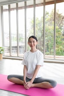 Van de de vrouwengreep van de portret jonge aziatische vrouw de yogamat na gebeëindigde klasse met exemplaarruimte