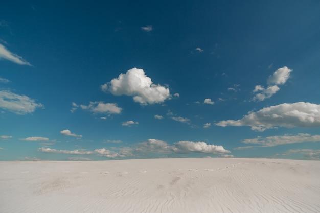 Van de de woestijn de blauwe hemel van het landschapszand witte wolken
