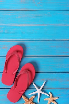 Van de de zeesterzomer van flipflops de zeeschelp blauwe houten verticaal als achtergrond