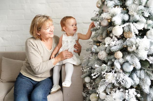Van de kerstmisfamilie, grootmoeder en baby meisjeszitting dichtbij kerstmisboom op de bank, vakantieconcept
