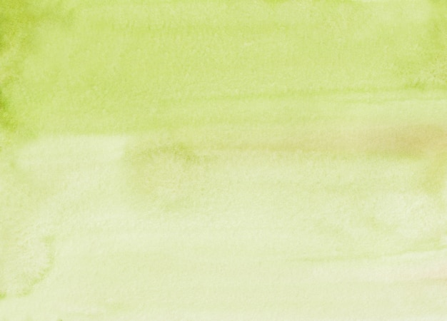 Van de waterverf lichtgeel groene kleur textuur als achtergrond. aquarel limoen overlay handgeschilderd. vlekken op papier.