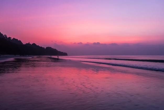 Van de zee silhouet van tallinn met vuur zee zonsondergang. prachtige zonsondergang aan zee in rood oranje violet kleuren.