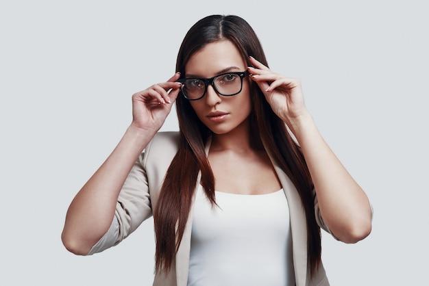 Van dichtbij bekijken. aantrekkelijke jonge vrouw die naar de camera kijkt en een bril aanpast terwijl ze tegen een grijze achtergrond staat