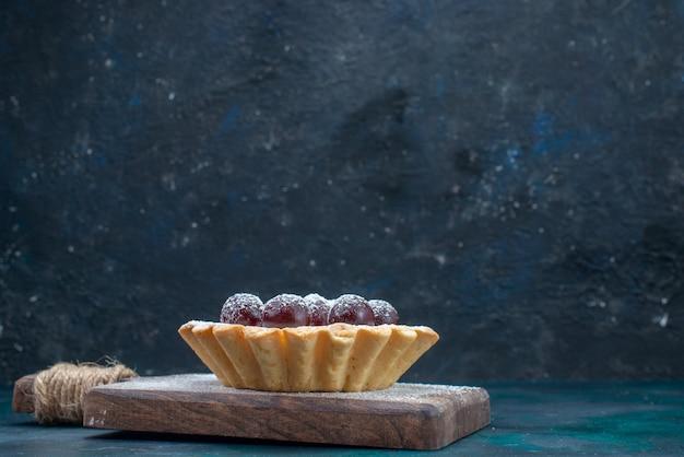 Van dichtbij bekijken kleine cake met fruit en suikerpoeder op donker
