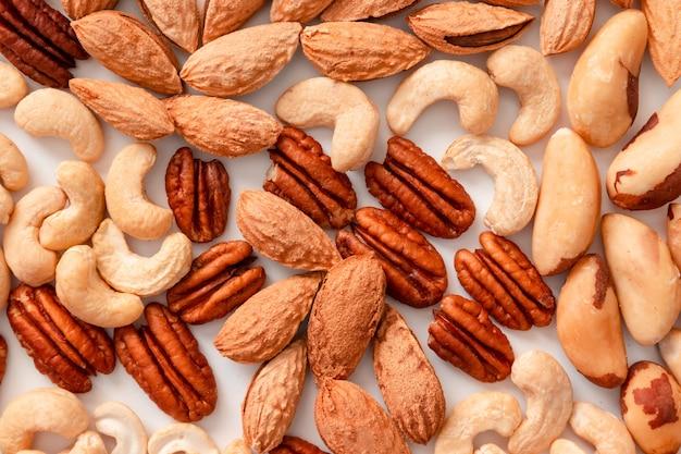 Van diverse noten pecannoten, macadamis, paranoot, cashewnoten, amandelen op een grijze ondergrond
