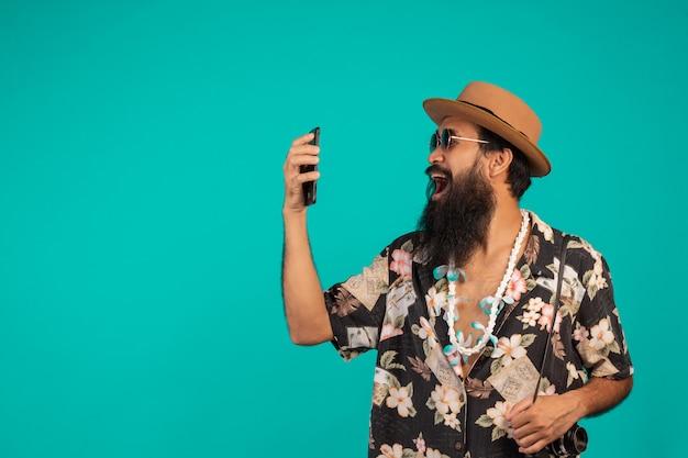 Van een gelukkige lange baardman die een hoed draagt, een gestreept shirt draagt, een telefoon vasthoudt aan een blauw.