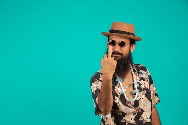 Van een gelukkige man met een lange baard die een hoed draagt, een gestreept shirt draagt dat een gebaar op een blauw toont.