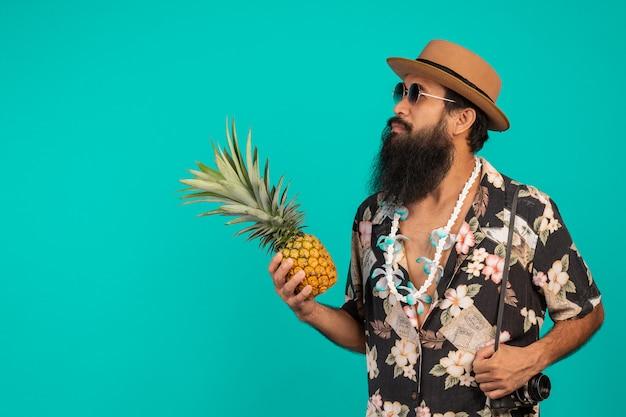 Van een mannelijke toerist met een lange baard die een hoed draagt en het effect op een blauw houdt.
