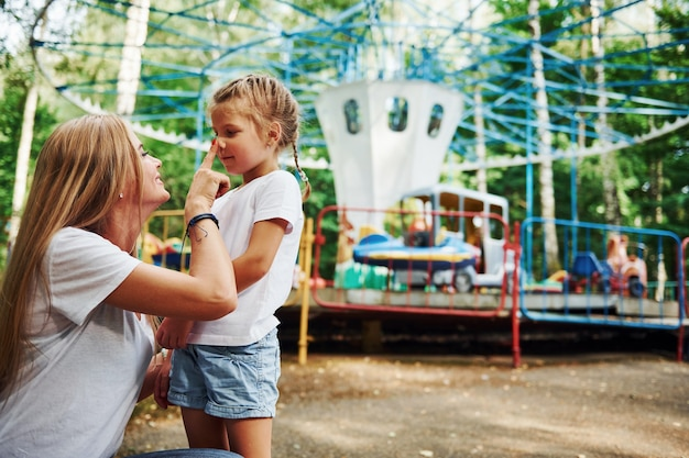 Van elkaar houden. vrolijk meisje haar moeder heeft een goede tijd samen in het park in de buurt van attracties.