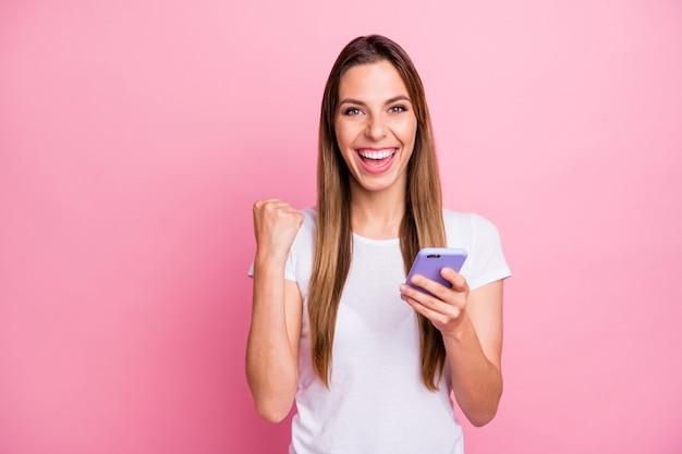 Van grappige dame houdt telefoonhanden check nieuw sociaal netwerk blog volgelingen reposts houdt van vieren grote cijfers dragen casual wit t-shirt