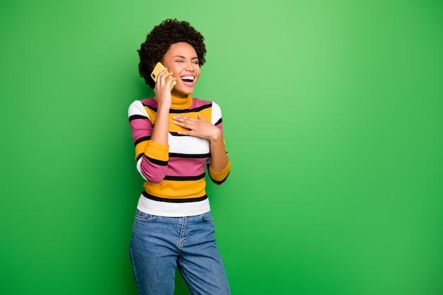 Van grappige vrolijke donkere huid golvende dame bedrijf telefoon in de buurt van oor spreken beste vriend luister coole grappen verhalen draag casual gestreepte jumper jeans