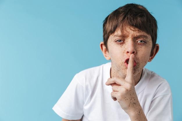 Van jonge jongen met sproeten, gekleed in een wit casual t-shirt met wijsvinger op lippen geïsoleerd over blauwe muur