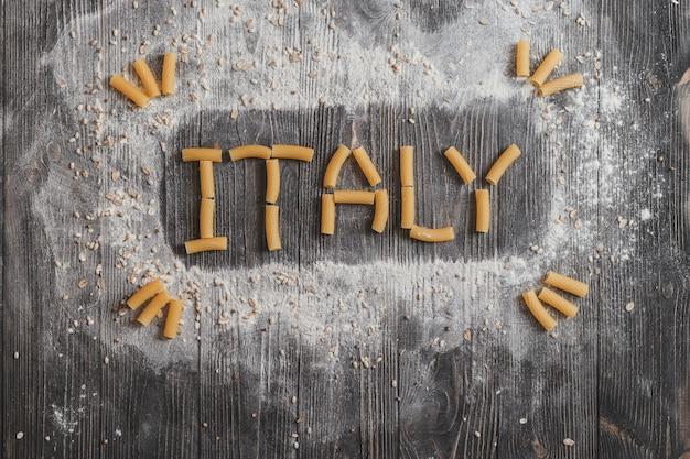 Van letters voorziende italië deegwaren op zwarte rustieke houten achtergrond. bovenaanzicht