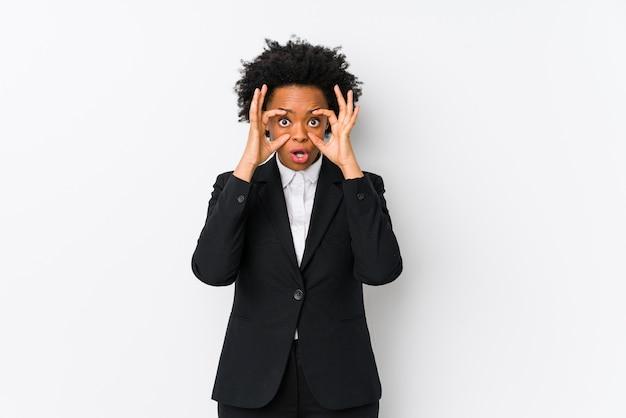 Van middelbare leeftijd afrikaanse amerikaanse bedrijfsvrouw tegen een witte muur die ogen openhoudt om een succeskans te vinden.