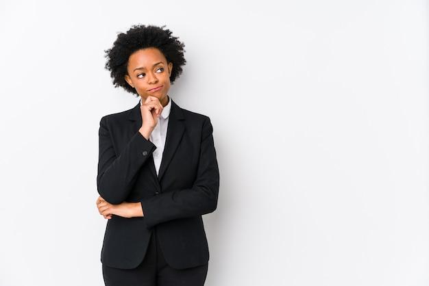 Van middelbare leeftijd afro-amerikaanse zakenvrouw kijkt zijwaarts met twijfelachtige en sceptische uitdrukking.