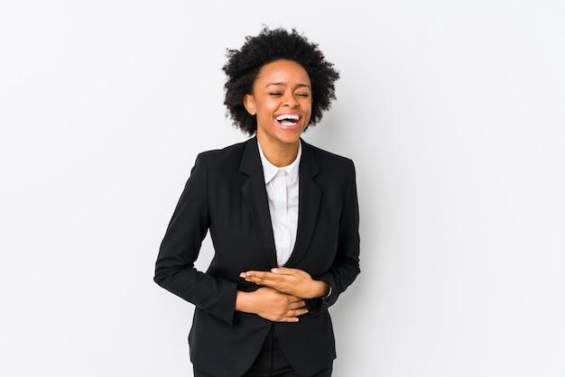 Van middelbare leeftijd afro-amerikaanse zakenvrouw tegen een witte achtergrond lacht vrolijk en heeft plezier bij het houden van de handen op de buik.
