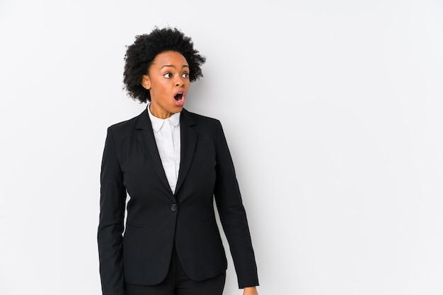 Van middelbare leeftijd afro-amerikaanse zakenvrouw tegen een witte muur geïsoleerd geschokt vanwege iets dat ze heeft gezien.