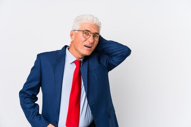 Van middelbare leeftijd blanke zakenman geïsoleerd aanraken achterkant van het hoofd, denken en het maken van een keuze.