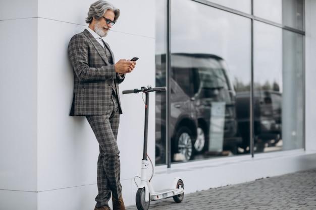 Van middelbare leeftijd zakenman rijden scooter in een stijlvol pak