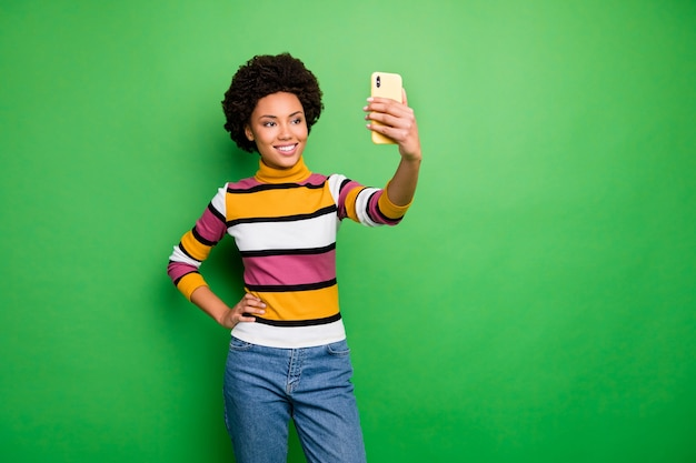 Van mooie donkere huid krullende dame die telefoonhanden vasthoudt die selfies maken voor populaire online website blog dragen casual gestreepte pulloverjeans