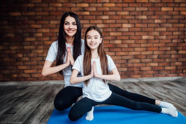 Van mooie moeder en dochter gymnastiek maken en thuis strekken. familie gezonde levensstijl.