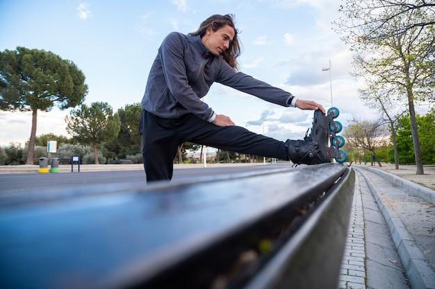 Van onder zijaanzicht van jonge coole man in sportkleding met rolschaatsen die zich uitstrekt over bank in park